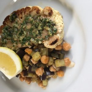 This is a photo of Cauliflower steak with cornishon salsa verde, eggplant & chick pea ragout