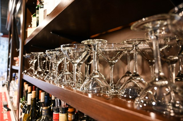 This is a photo of champagne glasses lined up and stored on a shelf in the bar area at the Federal.