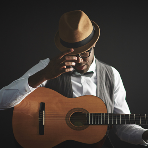 This is a stock photo of a man playing an acoustic guitar.